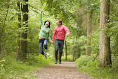Couple jumping on path holding hands and smiling Stock Photography