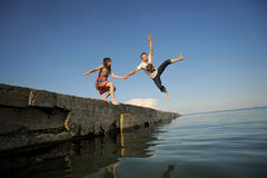 Couple jumping from a pier Stock Image