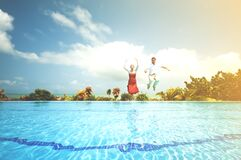 Couple jumping into pool Stock Photography