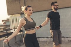 Couple jumping ropes. Couple exercising on a building rooftop terrace, jumping ropes royalty free stock photos