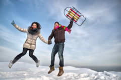 Couple jumping with sleigh. Royalty Free Stock Images