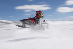 Couple Jumping Snowmobile In Snow. Side view of a couple jumping snowmobile in snow Stock Photo