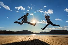 Couple jumping in the sun stock photography