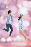 Couple jumping together against a bokeh background Royalty Free Stock Photography