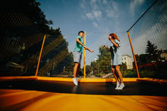 Couple jumping on trampoline in the park Stock Images