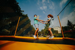 Couple jumping on trampoline in the park Stock Image