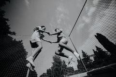 Couple jumping on trampoline in the park Royalty Free Stock Images