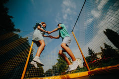 Couple jumping on trampoline in the park Royalty Free Stock Image