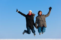 Couple jumping on a winter day Stock Images
