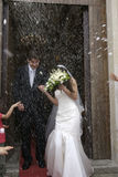 Couple just married. Under a rain of rice Stock Photo