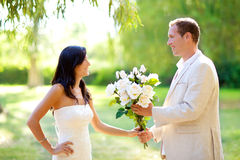 Couple just married with man holding flowers Royalty Free Stock Photo