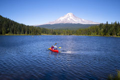 Couple on kayak rowing Trillium Lake with view of Mount Hood. Couple wearing hats active resting outdoor on the beautiful Trillium Lake recreation, rowing on the Royalty Free Stock Images