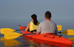 Couple Kayaking. On still water in a bright orange kayak stock photography