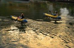 Couple Kayaking. A couple kayak on a lake at sunset Stock Images