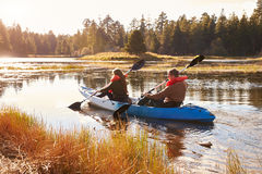 Couple kayaking on lake, back view, Big Bear, California Royalty Free Stock Photo