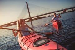 Couple kayaking on sunset Stock Photos