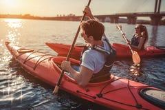 Couple kayaking on sunset Stock Images