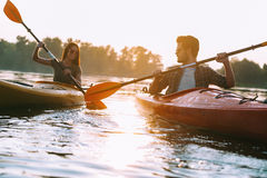 Couple kayaking together. Beautiful young couple kayaking on lake together and smiling Stock Images