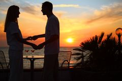 Couple keep for hands against sunset on sea Stock Photography