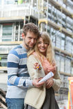 Couple with keys on front of new modern house Stock Photography