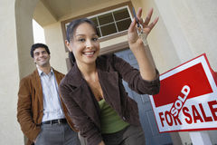 Couple With Keys To New Home. Happy couple with keys to new home by sold signboard stock photos