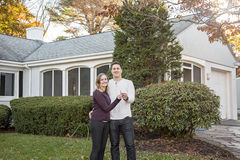 Couple with keys to new home. Smiling young couple standing in front of a new home holding keys royalty free stock photos
