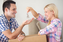 Couple with the keys to their new home. Moving into new home young happy couple, girl holding house keys and giving her boyfriend Royalty Free Stock Photos