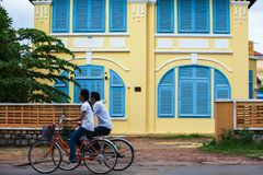 Couple Khmer teens riding bicycle pass old french colonial building. Scenic landscape town of Kampot, South Cambodia royalty free stock photo