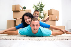 Couple with a kid in their new home laying on the floor with car. Happy couple with a kid in their new home laying on the floor royalty free stock photo