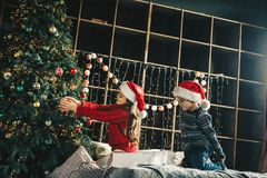 Couple kids Little girl and boy  in santa klaus hat decorating Royalty Free Stock Photos