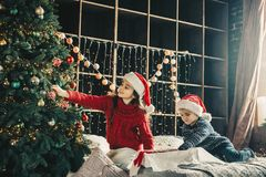 Couple kids Little girl and boy  in santa klaus hat decorating Stock Photo