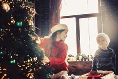 Couple kids Little girl and boy  in santa klaus hat decorating Stock Images