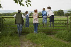 Couple With Kids Looking At Lush Landscape By Fence Royalty Free Stock Photos
