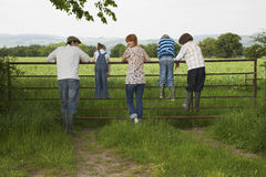 Couple With Kids Looking At Lush Landscape By Fence. Full length rear view of couple with three children looking at lush landscape by fence Royalty Free Stock Photos