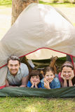 Couple with kids lying in the tent at park Royalty Free Stock Image