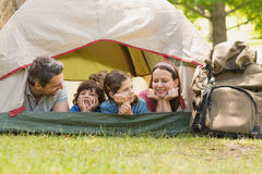 Couple with kids lying in the tent at park Stock Images