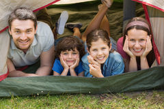 Couple with kids lying in the tent at park Royalty Free Stock Photo