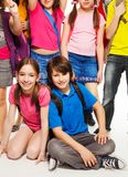 Couple kids sitting among friends Stock Photography
