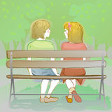 couple of kids sitting on a park bench Stock Image