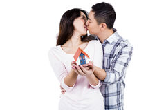 Couple kising while holding a model house Royalty Free Stock Images