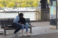 Couple kiss on a bench on the embankment on the Thames royalty free stock photos