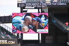 Couple on Kiss Cam. Couple kissing on Kiss Cam at a baseball game stock photography