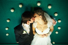 Couple kisses on the billiard table surrounded with white balls stock image