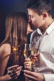 Couple kisses celebrating New Year`s eve drinking champagne and lighting up sparklers. On the party Stock Photo