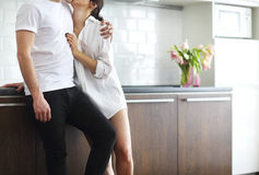 Couple kisses and hugs at kitchen in the morning Stock Photos