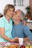 Couple kissing. At breakfast in the kitchen Royalty Free Stock Photography