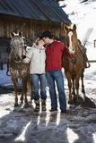 Couple kissing. Caucasian couple kissing and holding horses with stable in background Royalty Free Stock Photography