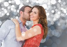 Couple kissing against silver bokeh background. Romantic couple kissing against silver bokeh background Royalty Free Stock Photography