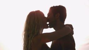 Couple kissing against sunlight
