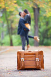 Couple kissing at alley. Couple with suitcase kissing at alley in the park Stock Photography